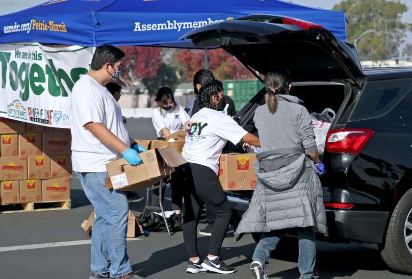Volunteers help load boxes of food into vehicles at the Power of One Foundation Thanksgiving food giveaway on Saturday.