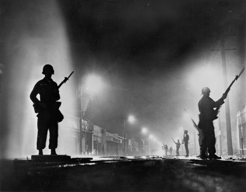National Guard troops secure a stretch of 103rd Street, dubbed Charcoal Alley, in Watts to help L.A. authorities restore order on August 13, 1965. The riots, sparked by the arrest of a black motorist for drunk driving, lasted for six days.