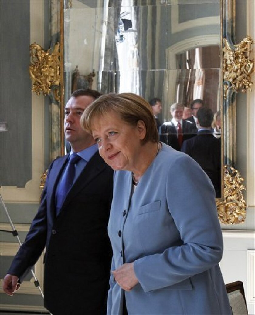 German Chancellor Angela Merkel, right, and Russian President Dmitry Medvedev arrive for bilateral talks at the government guest house Schloss Meseberg,north of Berlin, Saturday, June 5, 2010. (AP Photo/Tobias Schwarz, Pool)