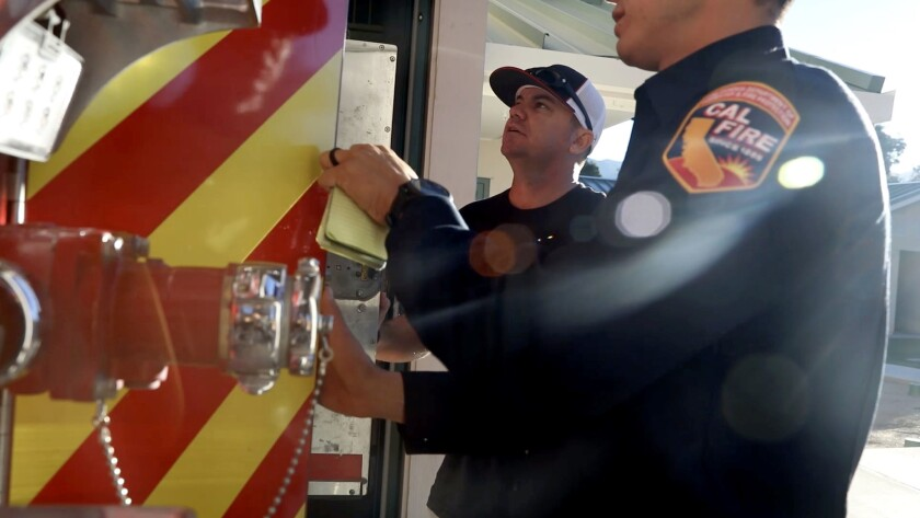Jason McMillan, left, a San Diego-based Cal Fire firefighter returns to work after a trauma retreat.