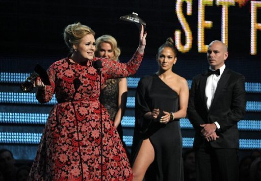 """Adele, left, accepts the award for best pop solo performance for """"Set Fire to the Rain"""" at the 55th annual Grammy Awards on Sunday, Feb. 10, 2013, in Los Angeles. Looking on from right are presenters Pitbull and Jennifer Lopez. (Photo by John Shearer/Invision/AP)"""