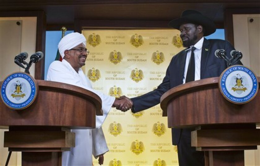 Sudan's President Omar al-Bashir, left, and South Sudan's President, Salva Kiir, right, shake hands at a joint press conference in Juba, South Sudan Friday, April 12, 2013. Sudanese President Omar al-Bashir traveled to South Sudan on Friday for the first time since the south peacefully broke away f