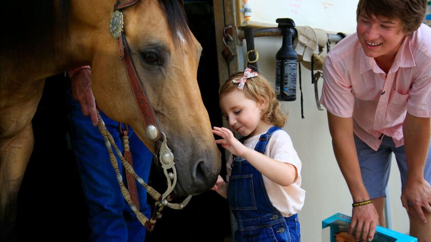 At the Roper Ranch in San Marcos, Ryan Melendez (right) introduces Ivy Fondots to her warrior horse,