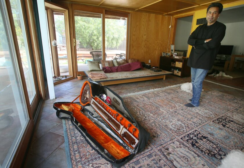 Kartik Seshadri at his Encinitas home with his sitar he said was damaged during a British Airlines flight last September.