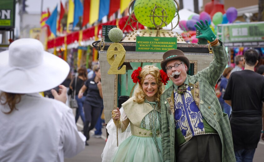 """Valerie Hager, center, as Ozma, and Jerry Hager, right, as Oz, The Great and Powerful, pose for a fairgoer's photograph Friday, which was opening day at the """"Wizard of Oz""""-themed San Diego County Fair."""