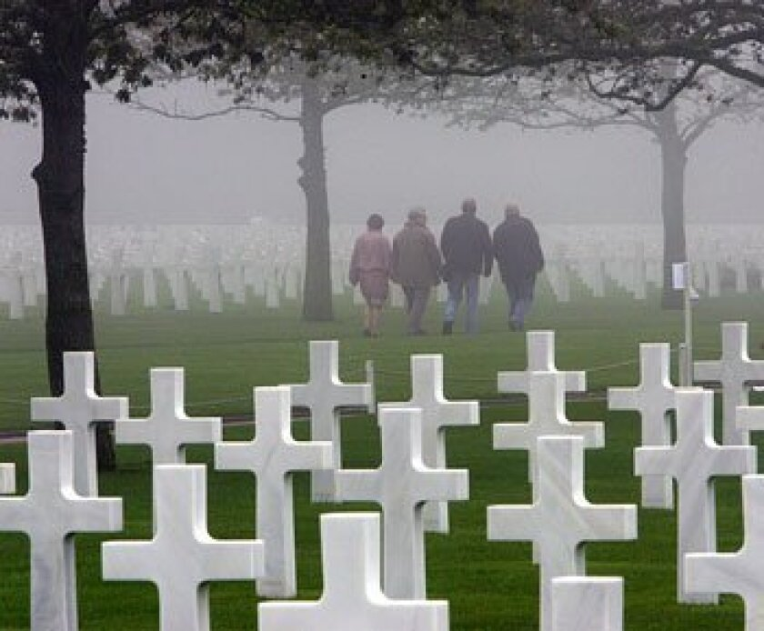 Visitors walk among the white marble crosses at the American Cemetery in Colleville-sur-Mer.  (Remy de la Mauviniere / Associated Press)
