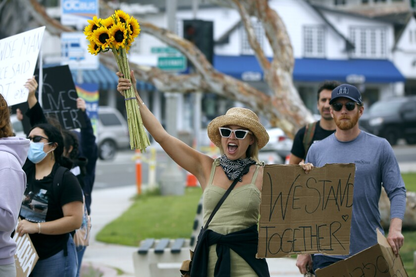 Helen Kramer, 28, brought flowers and a sign to a Black Lives Matter protest at Main Beach Park.