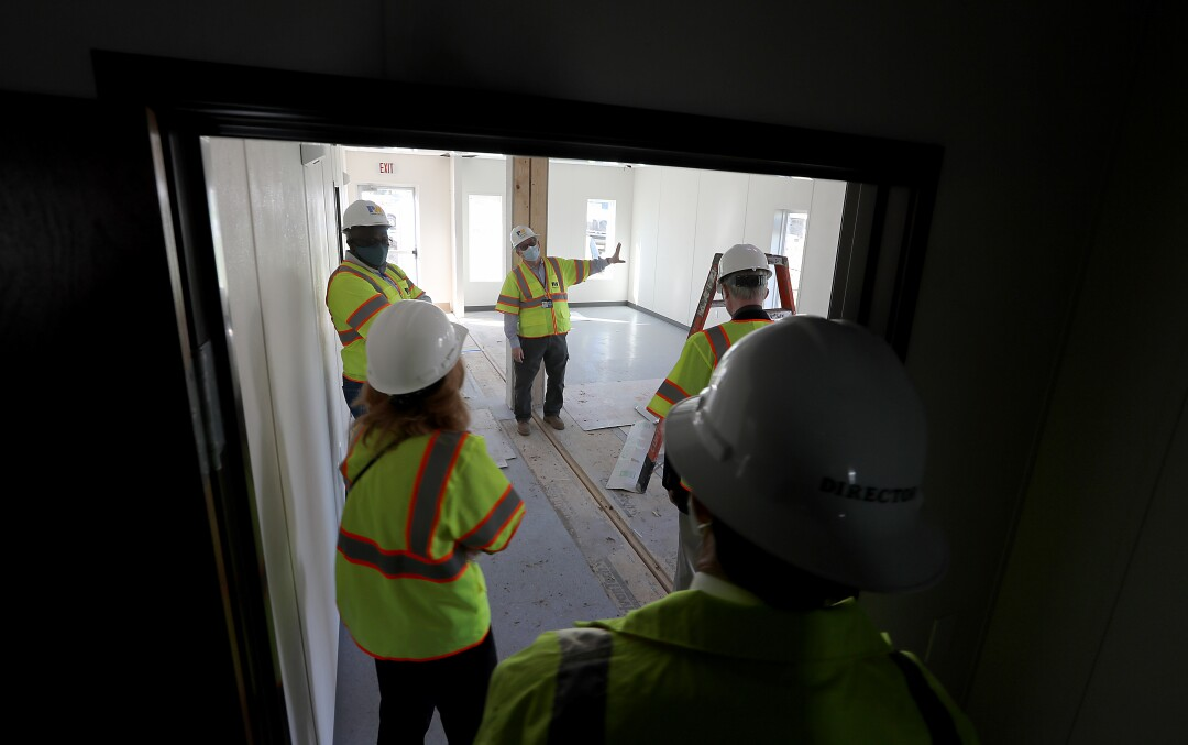 L.A. County officials and contractors tour the site of a homeless housing project.