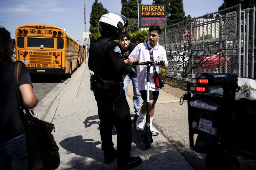 An LAPD bike officer warns two young men about riding their e-scooters on the sidewalk, in front of Fairfax High School near the intersection of Fairfax and Melrose avenues on Thursday.