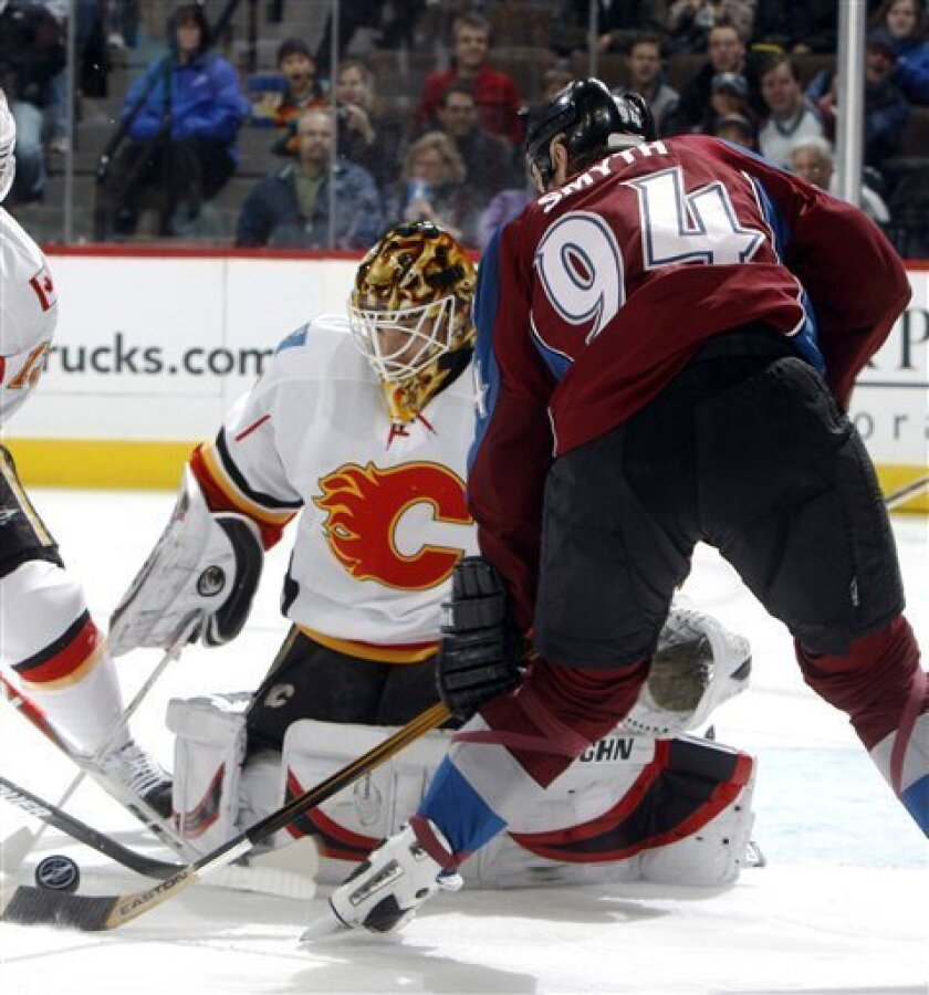 Calgary Flames goalie Curtis McElhinney, left, makes a stick save on a shot by Colorado Avalanche left winger Ryan Smyth (94) in the first period of an NHL hockey game in Denver on Sunday, Jan. 18, 2009. (AP Photo/David Zalubowski)