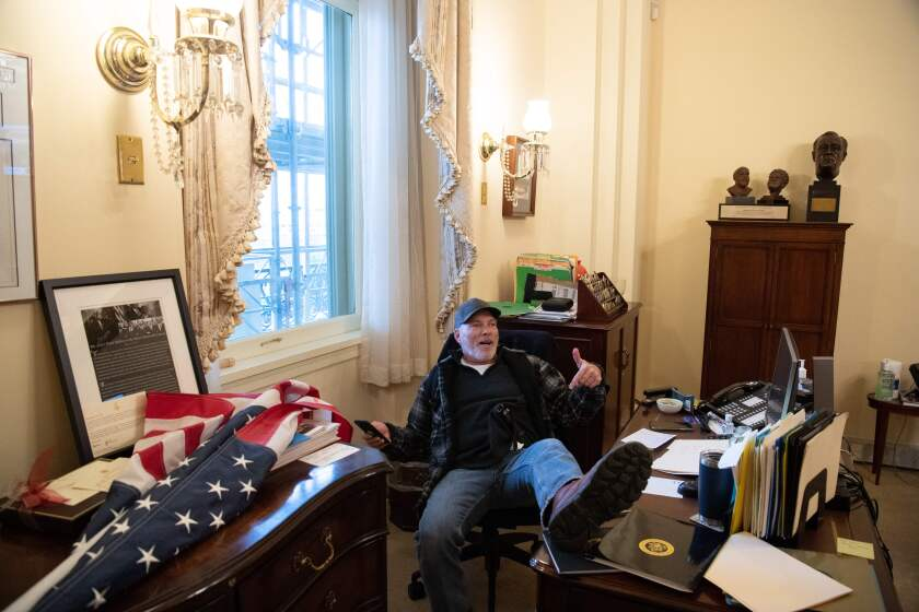 A man leans back in an office chair with his foot on the desk in a congressional office