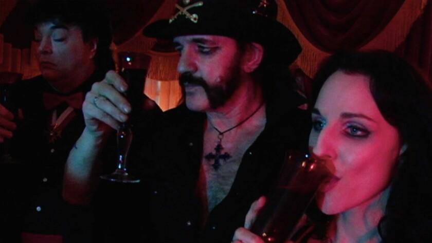 "Lemmy Kilmister, center, and Phoebe Dollar in the film ""Sunset Society."""