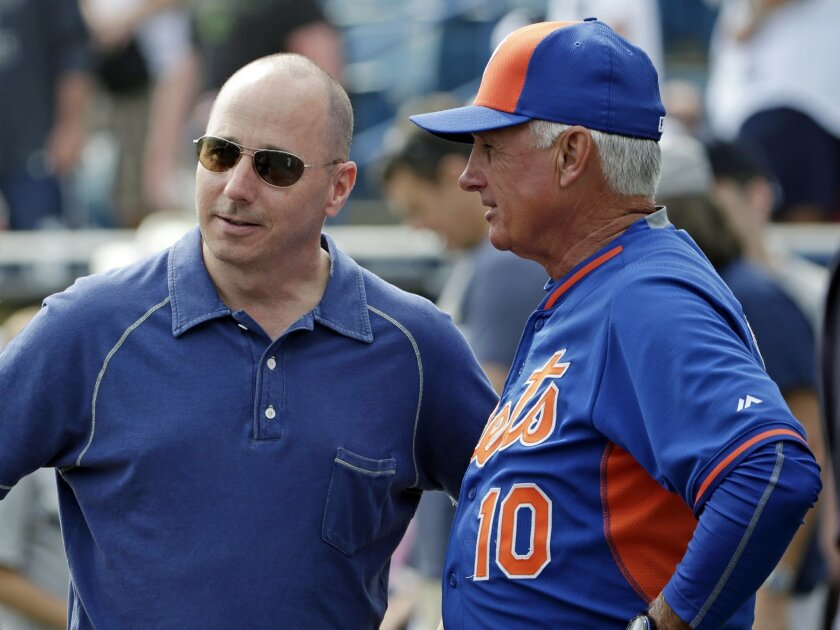 FILE - In this Wednesday, March 25, 2015 file photo, New York Yankees general manager Brian Cashman, left, talks to New York Mets manager Terry Collins before an exhibition baseball game in Tampa, Fla. For the first time in the four decades of baseball's modern economic era, the Yankees enter sprin
