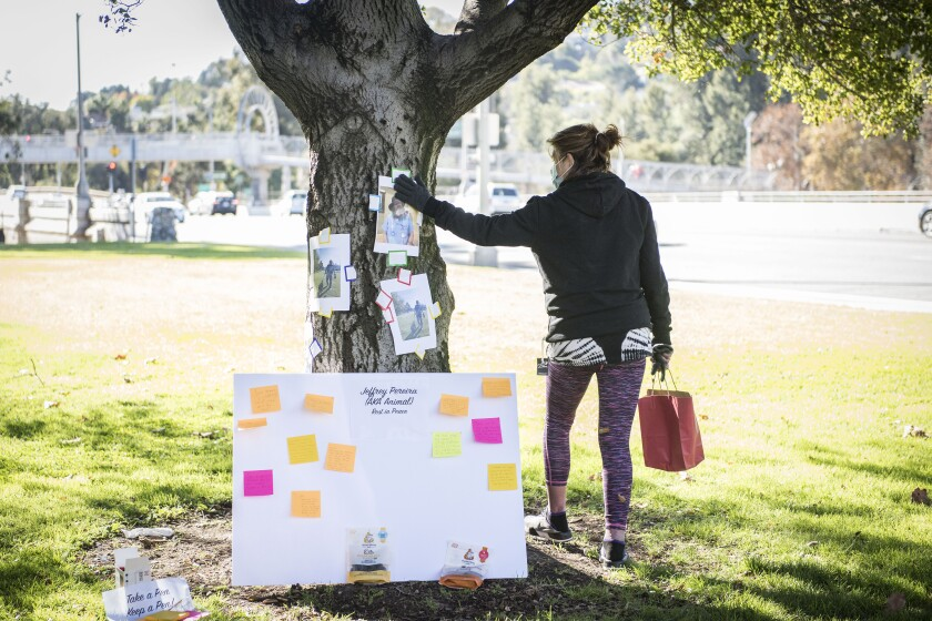 Cynthia Caldwell, a neighbor of Jeffrey Pereira in the homeless encampment, touches his photo at a vigil in Bond Park.