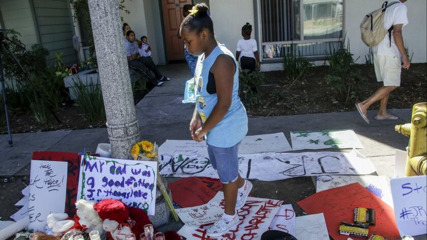 Raquel Thomas, then 9, pays her respects in 2016 at a makeshift memorial for her father, Reginald Thomas Jr.