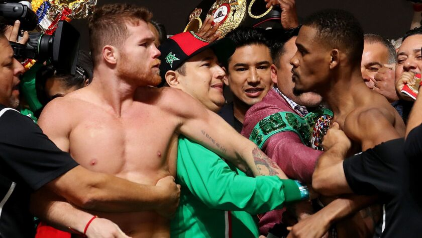 Canelo Alvarez and Daniel Jacobs get into a shoving match during their official weigh in at T-Mobile Arena.