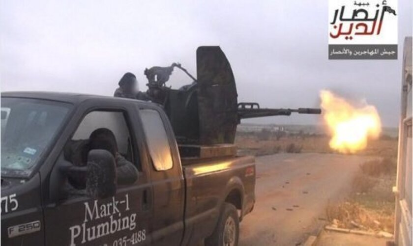This image, apparently showing Chechen Jaish al Muhajireen wal Ansar fighters in combat against Syrian government forces in Aleppo, is from the Twitter feed of Caleb Weiss (@Weissenberg7). The tweet, dated Dec. 15, 2014, is seen in a lawsuit from the previous owner of the pickup truck. The truck's