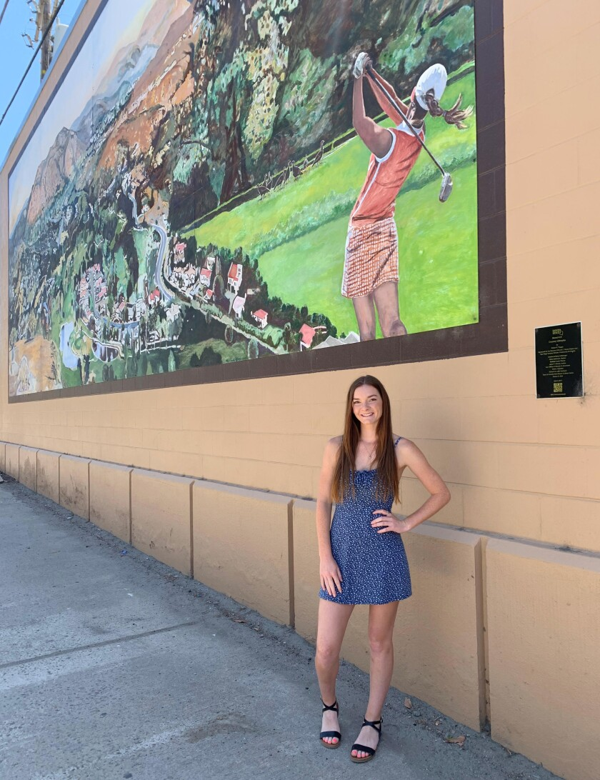 """Hannah Anderson's image can be seen swinging a golf club in the """"Country Lifestyle"""" mural at 10th and Main streets."""