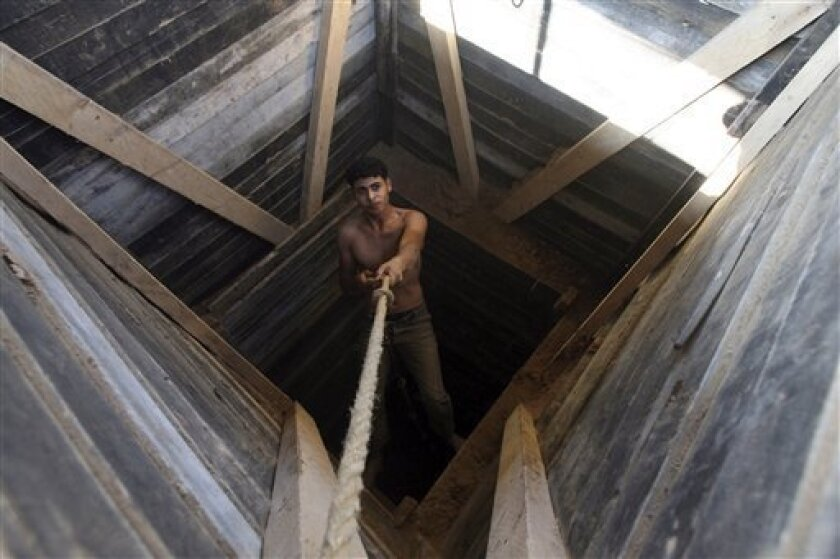 A Palestinian lowers himself into a tunnel on the border with Egypt and Rafah in the southern Gaza Strip, Thursday, Dec. 10, 2009. Israel and Egypt have blockaded Gaza since the militant group Hamas seized power there in 2007. Gaza residents use tunnels to haul in supplies from Egypt. (AP Photo/Eyad Baba)