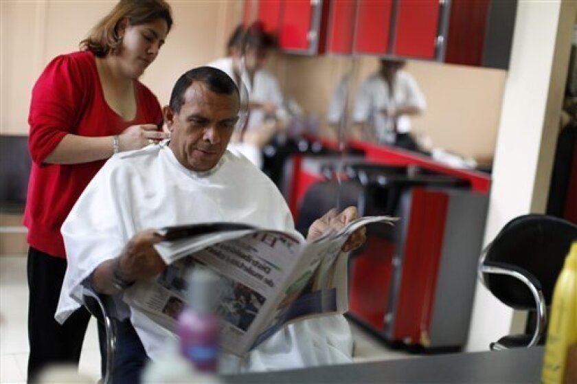 Porfirio Lobo, candidate for president for Honduras' National Party, reads a newspaper in a barber shop in Tegucigalpa, Friday, Nov. 27, 2009. Honduras's general elections are scheduled for Nov. 29.  (AP Photo/Rodrigo Abd)