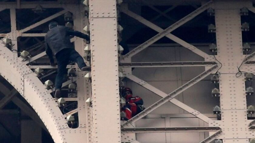 A man climbs the Eiffel Tower, Paris, France - 20 May 2019