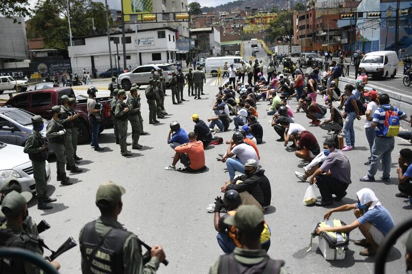 Miembros de la Guardia Nacional Bolivariana explican el uso de la mascarilla a peatones