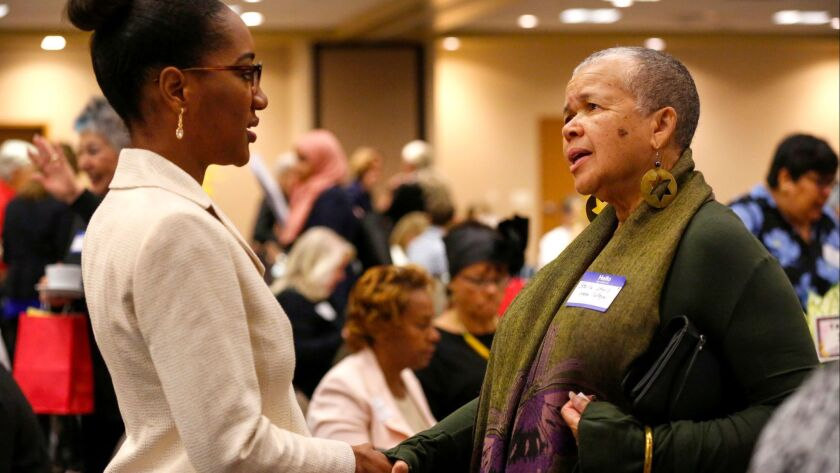 Nasheema Harvey, left, meets poet/author Starla Lewis prior to the start of the Indivisible WATU Women of Color ROAR breakfast at the Jacobs Center for Neighborhood Innovation on Saturday morning.
