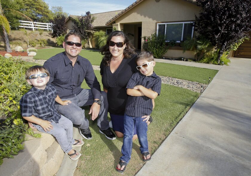 Justin and Krystal Lane and their sons Parker, left, and Brodi pose out front of their Valley Center home that they purchased with zero percent down about a year ago.