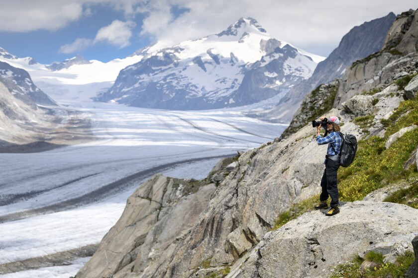 FILE - In this July 21, 2020 file photo, Swiss photographer David Carlier takes photographs of the Swiss Aletsch glacier, the longest glacier in Europe, on the sideline of his photographic exhibition, in Fieschertal, Switzerland. Climate change is increasingly damaging the U.N.'s most cherished heritage sites, a leading conservation agency warned Wednesday Dec. 2, 2020, reporting that Australia's Great Barrier Reef and dozens of other natural wonders are facing severe threats. (Laurent Gillieron/Keystone via AP, File)