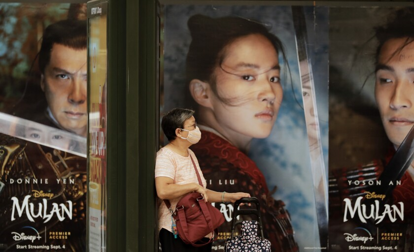 Movie posters serve as a backdrop for a mask-wearing passenger waiting for her bus on Broadway in Chinatown.