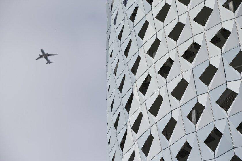 In this Oct. 30, 2015 photo, a passenger jet flies past the City View Garage in the Miami Design District in Miami. The garages wavy gold-and titanium-coated steel panels shimmer against the Miami sun. The Miami Design District is emerging as an upscale shopping and art mecca. (AP Photo/Wilfredo Le