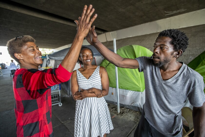 Beatrice Hart, left, gives a high-five to Edwin Williams as Michelle Vaughn watches. Hart recently moved into an apartment in Sunland but returns often to the camp, where she's the unofficial den mother.