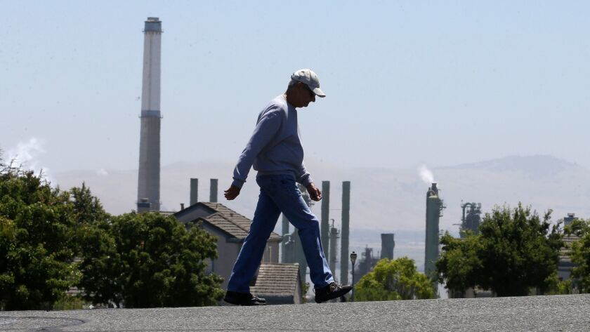 The stacks from the Valero Benicia Refinery are seen as a pedestrian walks in a nearby neighborhood,