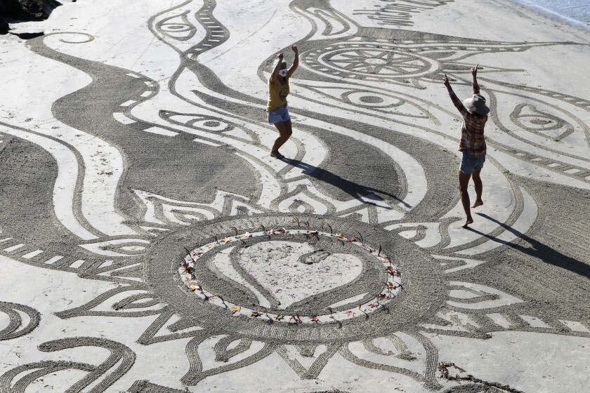 Sharon Belknap and Heather Nelson dance in their sand mandala at Cardiff State Beach on Wednesday.