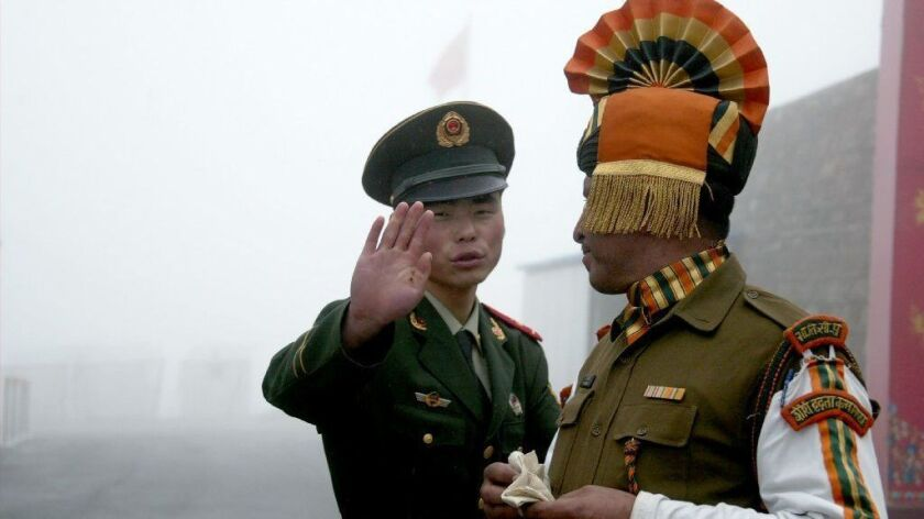A 2008 photo shows a Chinese soldier gesturing next to an Indian soldier at a border crossing.