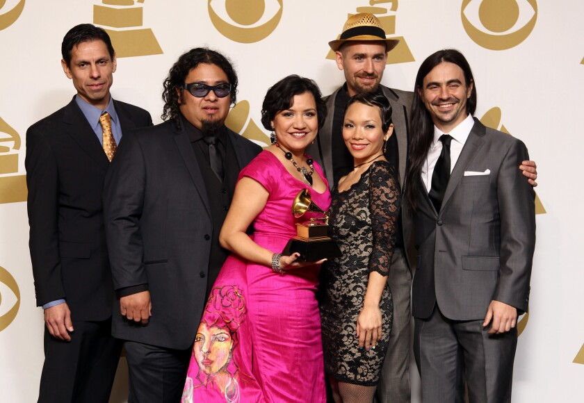 """Musical group Quetzal poses backstage with its award for Latin rock, urban or alternative album for """"Imaginaries"""" at the 55th Grammy Awards."""