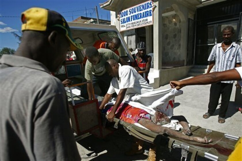 An earthquake victim is carried from a vehicle to a funeral home in Port-au-Prince, Haiti, Wednesday, Jan. 13, 2010. The 7.0-magnitude earthquake that hit Haiti on Tuesday flattened the president's palace, the cathedral, hospitals, schools, the main prison and whole neighborhoods. (AP Photo/Ricardo Arduengo)