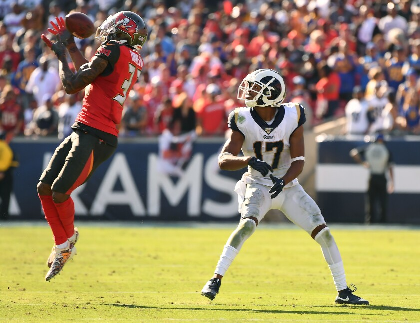Tampa Bay Buccaneers cornerback Carlton Davis, left, intercepts a pass intended for Rams wide receiver Robert Woods during the fourth quarter on Sunday.