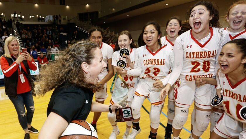 Cathedral Catholic players celebrate their victory over Mission Hills in the Open Division final with coach Jackie Turpin (left).