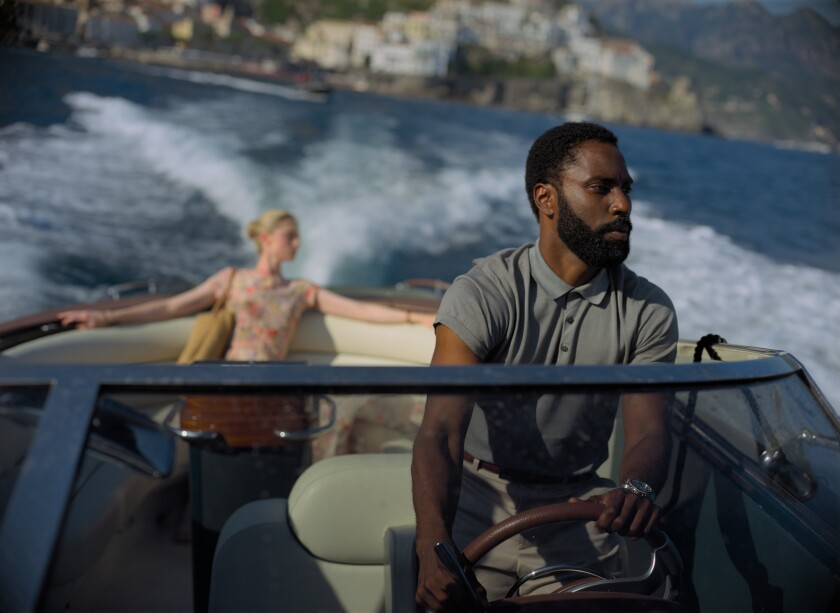 "This image released by Warner Bros. Entertainment shows Elizabeth Debicki, left, and John David Washington in a scene from ""Tenet."" As ""Tenet"" enters its third week in North American cinemas with barely any new blockbusters on the horizon, U.S. exhibitors are put in a tricky spot. (Melinda Sue Gordon/Warner Bros. Entertainment via AP)"