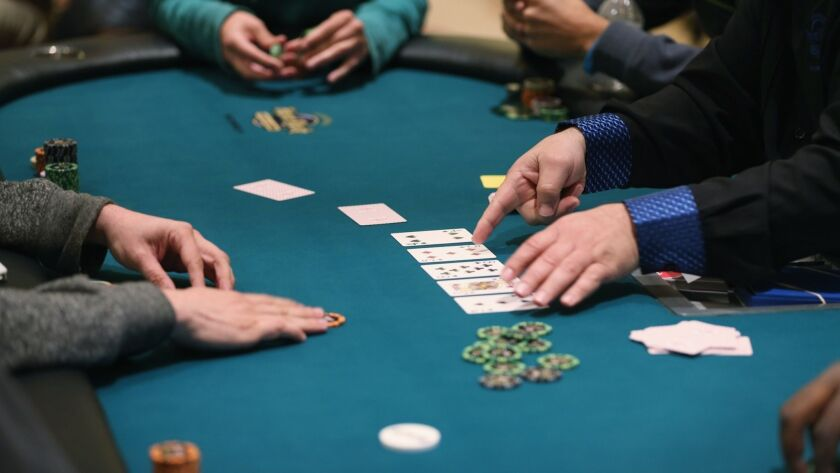Participants play their hands at a poker event in Hollywood, Fla., in 2014.