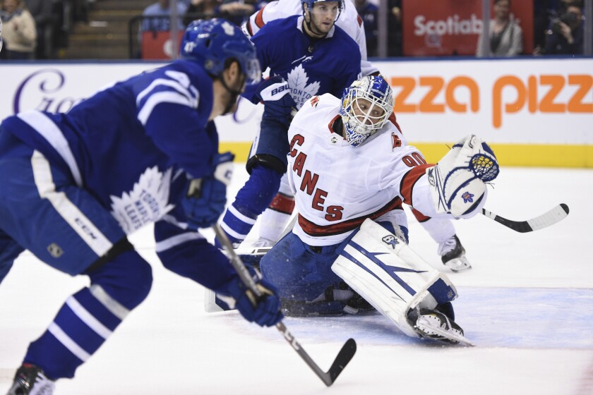 David Ayres playing goalie for the Carolina Hurricanes, with two Toronto Maple Leafs.