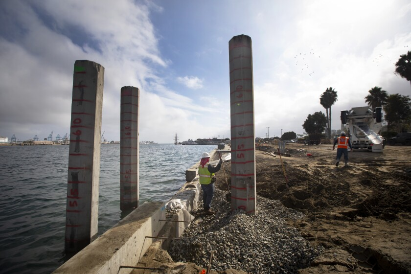 Crews at a construction site with concrete pillars next to the harbor
