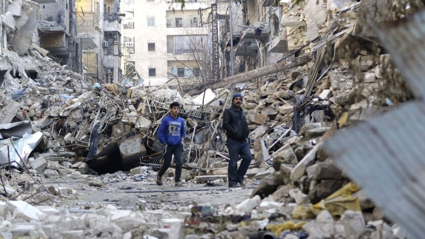 Two people walk amid destroyed buildings in Aleppo, Syria's formerly rebel-held al-Shaar neighborhood, on Jan. 21, 2017.