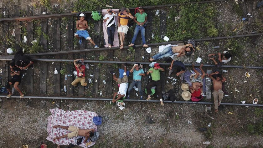 Central American migrants who are part of a caravan slowly making its way toward the U.S.-Mexico border rest on railroad tracks in Arriaga, Mexico, on Oct. 26, 2018.