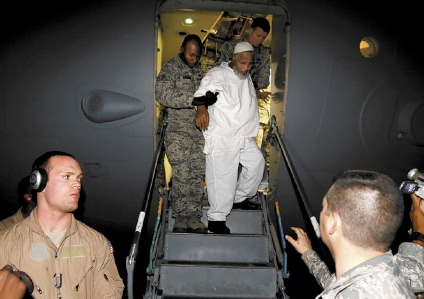 Ibrahim Othman Ibrahim Idris is escorted Thursday off a U.S. military plane in Khartoum, Sudan, after his release from the U.S. military prison at Guantanamo Bay, Cuba.