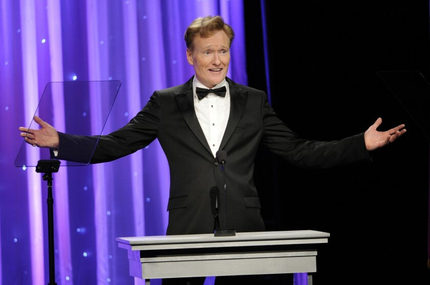 FILE - In this Oct. 8, 2014 file photo, Conan O'Brien addresses the audience during the 2014 Princess Grace Awards Gala in Beverly Hills, Calif. O'Brien will visit Harvard on Friday, Feb. 12, 2016, for a conversation about arts and education with university President Drew Faust followed by question
