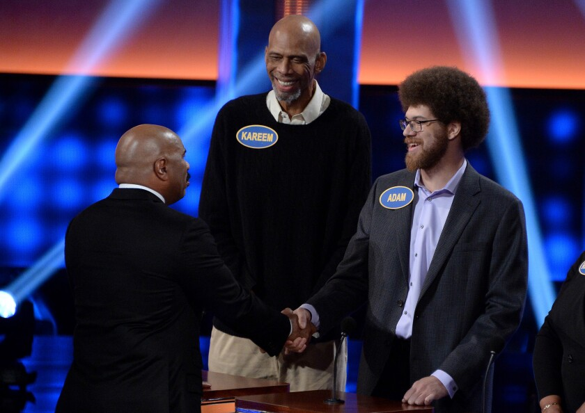 """Adam Abdul-Jabbar, right, shakes hand with """"Family Feud"""" host Steve Harvey, center, as Kareem Abdul-Jabbar looks on."""