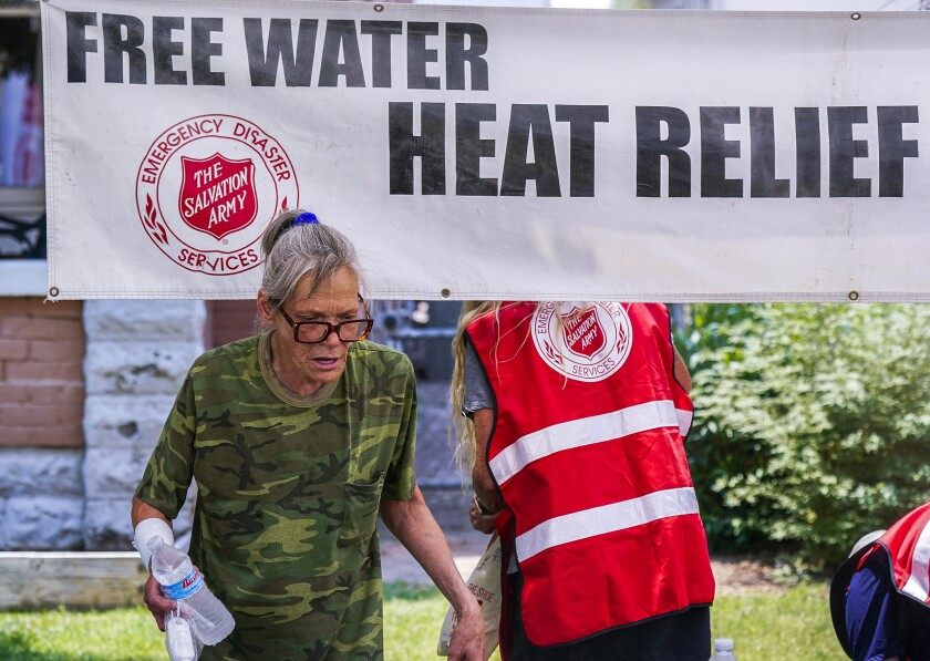 A pedestrian holds a bottle of cold water at a Salvation Army hydration station in Phoenix on June 15.