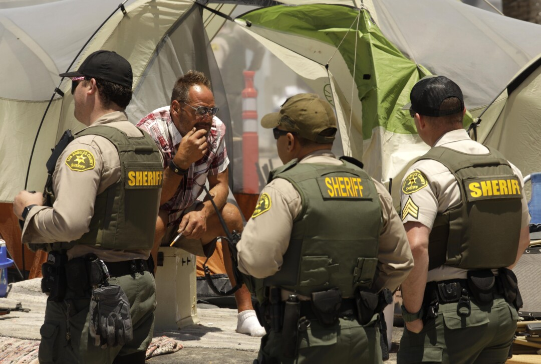 Sheriff's deputies with the Homeless Outreach Services Team engage with homeless people.